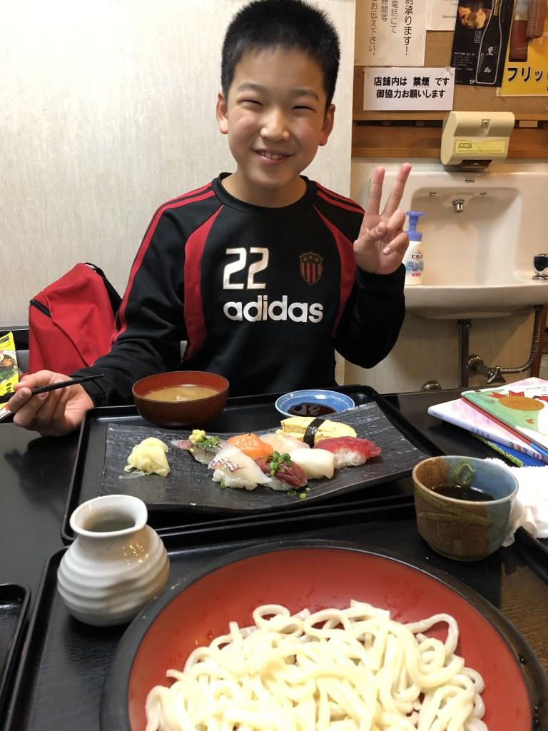 寿司を食べる笑顔の子ども