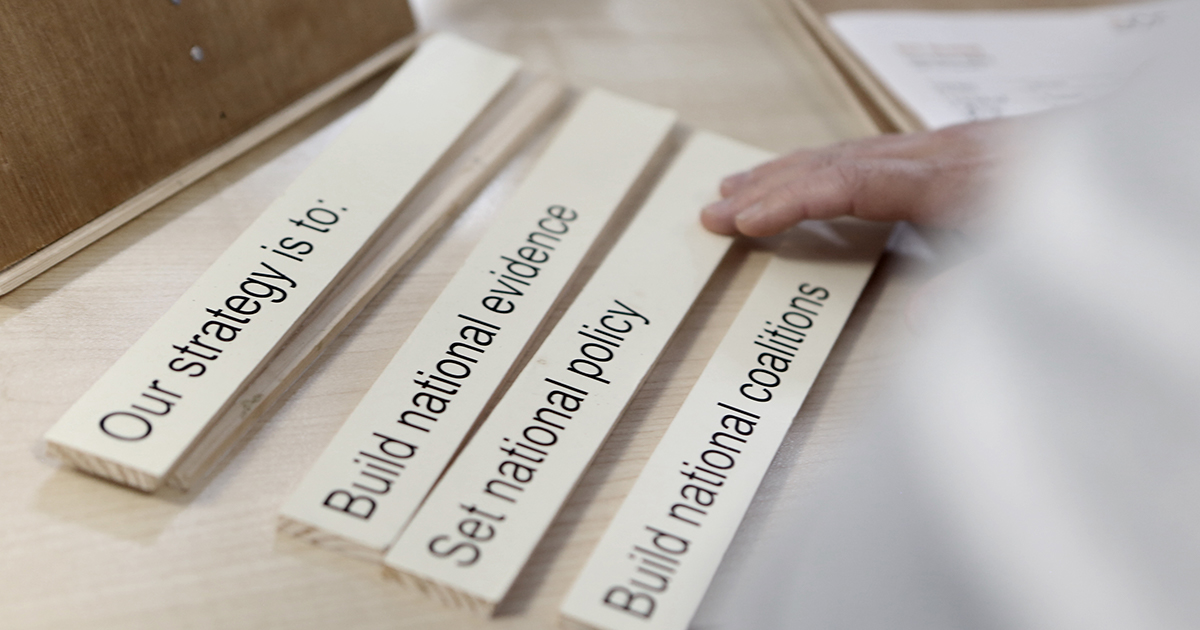 """Small wooden boards reading: """"Our strategy is to Build national evidence, Set national policy, Build national coalitions"""""""