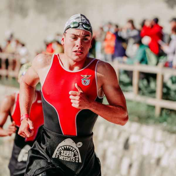 muscular sportsman running after swimming during competition