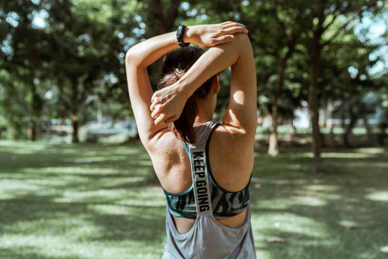 unrecognizable female athlete stretching muscles of arms and back
