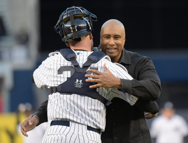 Bernie Williams, who won four World Series titles with the Yankees, with catcher Brian McCann after throwing a ceremonial pitch in the Bronx on May 24. (BILL KOSTROUN / ASSOCIATED PRESS)