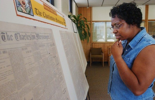 Cynthia Hurd, one of the nine churchgoers killed last week in the mass shooting at Emanuel AME Church, looks over a reproduction of the original of the Charleston Messenger found inside the John L. Dart Library in 2002. (Photo via postcourier.com)