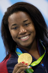 United States' Simone Manuel shows off her gold medal during the medal ceremony for the women's 100-meter freestyle final during the swimming competitions at the 2016 Summer Olympics, Friday, Aug. 12, 2016, in Rio de Janeiro, Brazil. (AP Photo/Michael Sohn)