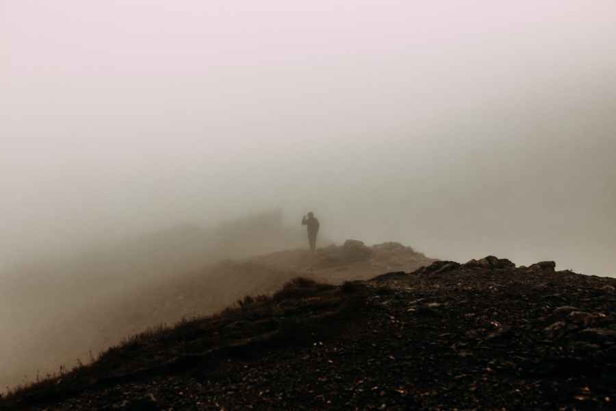 silhouette of person standing on hilltop in haze