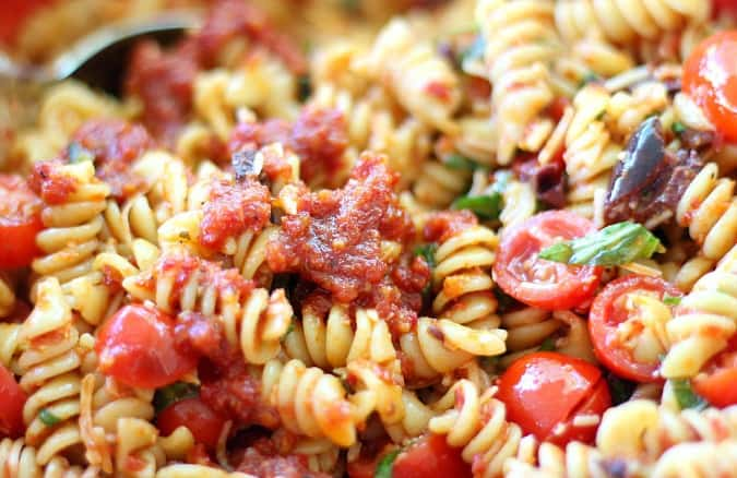 Pasta Salad with Sun-Dried Tomatoes, Basil and Parmesan Cheese, featuring fresh herbs, tomatoes and kalamata olives. Lots of Parmesan, of course!