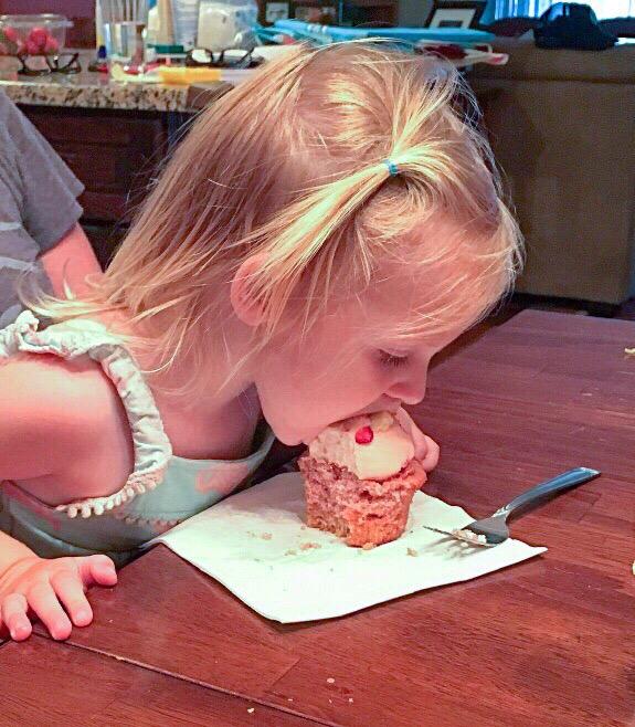 Evie eating a cupcake