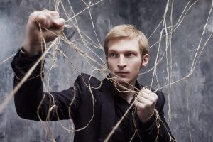 Control: Young man trying to pull his way out of a tangled web of strings