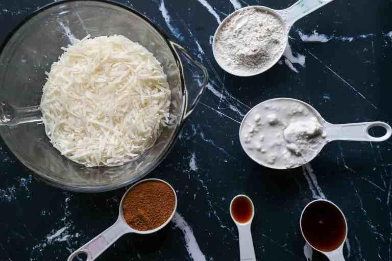Ingredients to make vegan coconut macaroons coconut cream, coconut sugar, maple syrup, vanilla extract, gluten free flour, coconut shavings