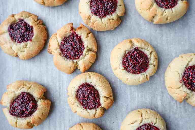 close up of raspberry jam filled thumbprint cookies