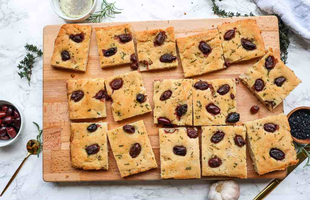 slices of gluten free focaccia with rosemary, garlic, and olives