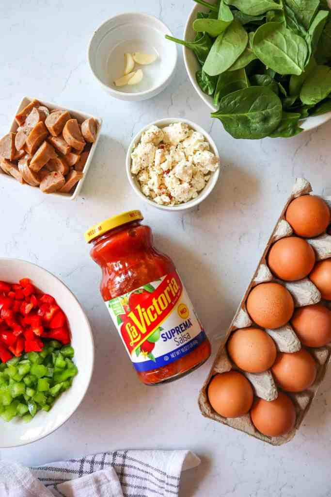 ingredients needed to make egg muffins: spinach, cheese, fresh garlic, eggs, LaVictoria Salsa, chopped peppers, sliced sausage