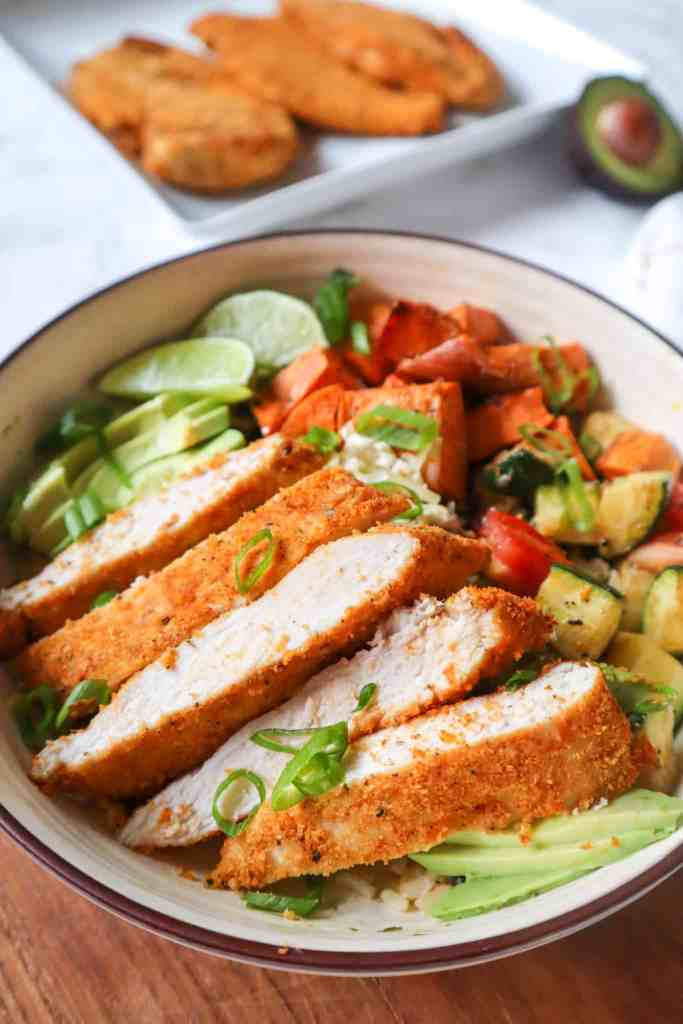 gluten free crispy air fryer chicken, sliced and added to a bowl with lentils, zucchini, sweet potato, avocado, and lime