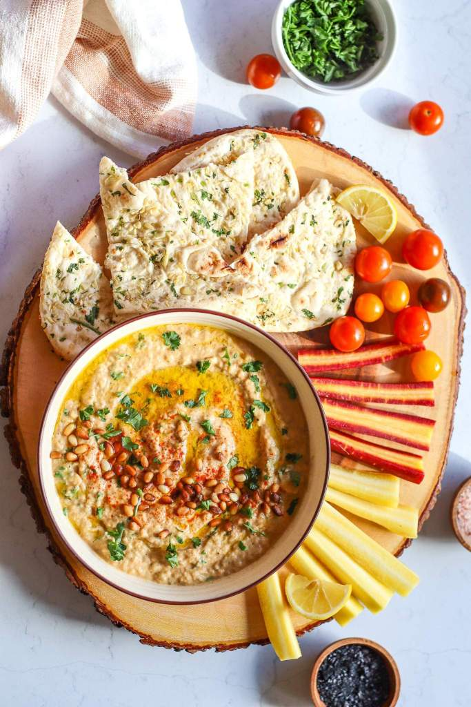 baba ganoush served with carrots tomatoes and pita bread