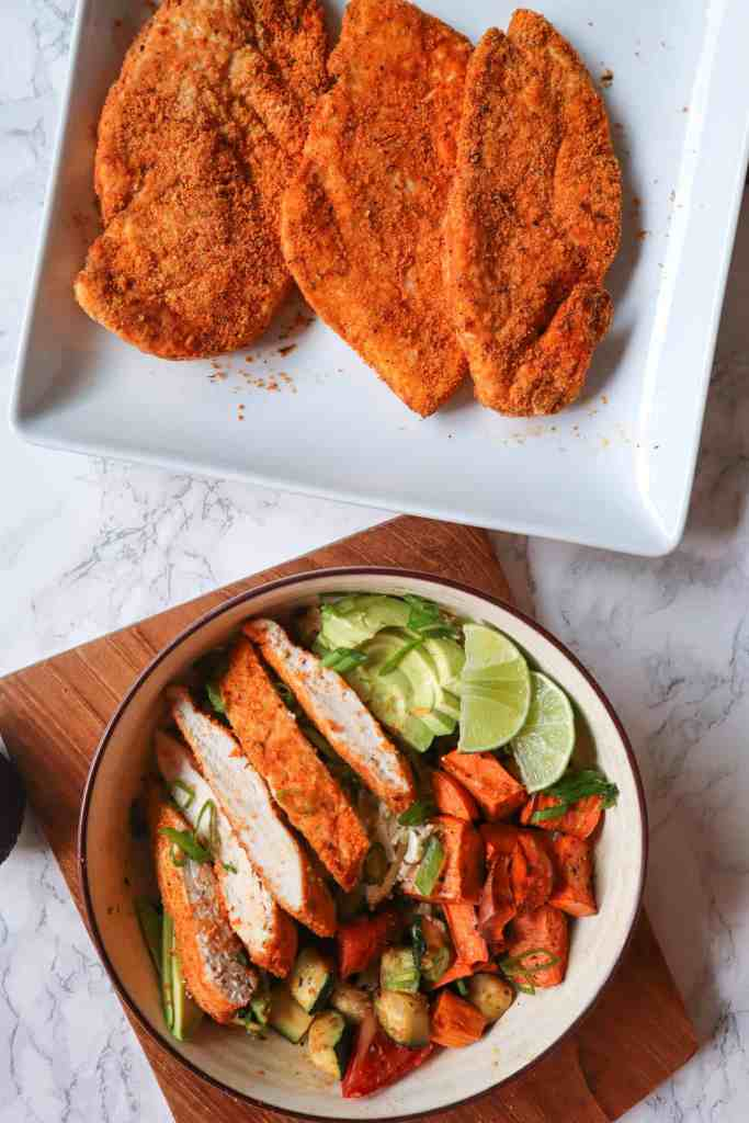 3 Crispy gluten free air fryer chicken breasts on a plate and a bowl of sliced chicken breast with rice, vegetables, lime, and avocado