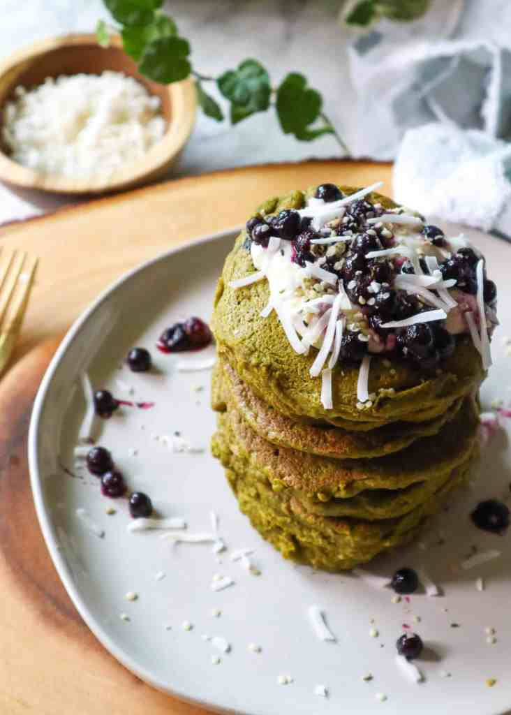 Moringa fluffy pancakes toped with blueberries, coconut, hemp seeds