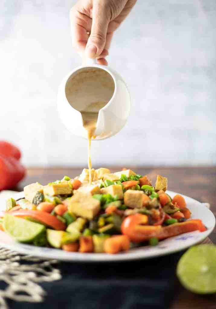 Stir fry in a plate with peanut sauce being poured on