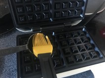 oiling the waffle iron with oil from measuring spoon
