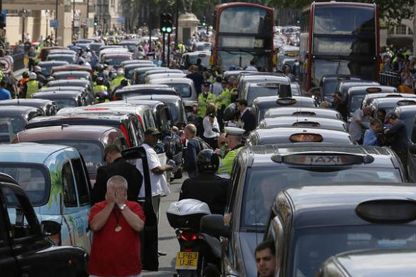 Taxi drivers block the road in Whitehall in central London June 11, 2014. While taxi drivers go on strike, Uber has seen an 850 percent increase in sign-ups for the app. Luke MacGregor/Reuters