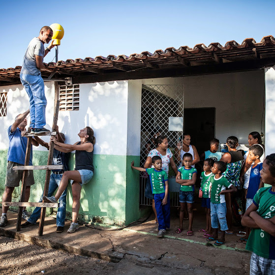 Project Loon team members setting up an antenna on the rooftop of a Brazillian School