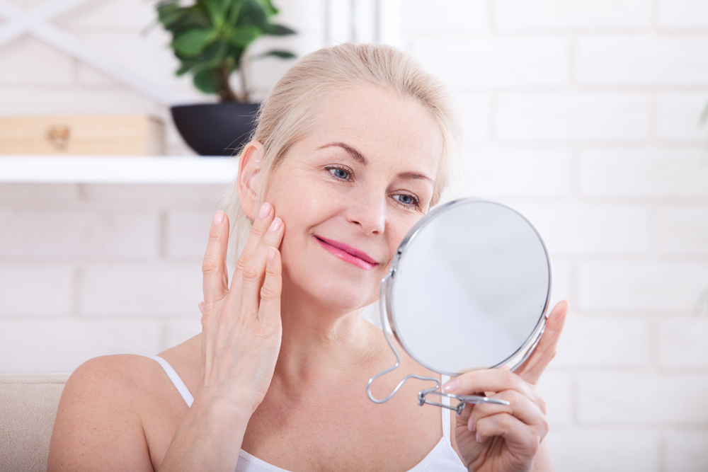 middle aged woman looking at wrinkles in mirror
