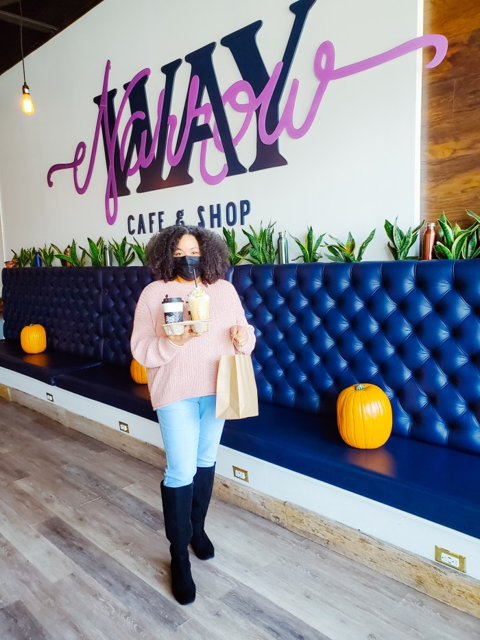 A woman holding coffee and a smoothie at Narrow Way Café in Detroit