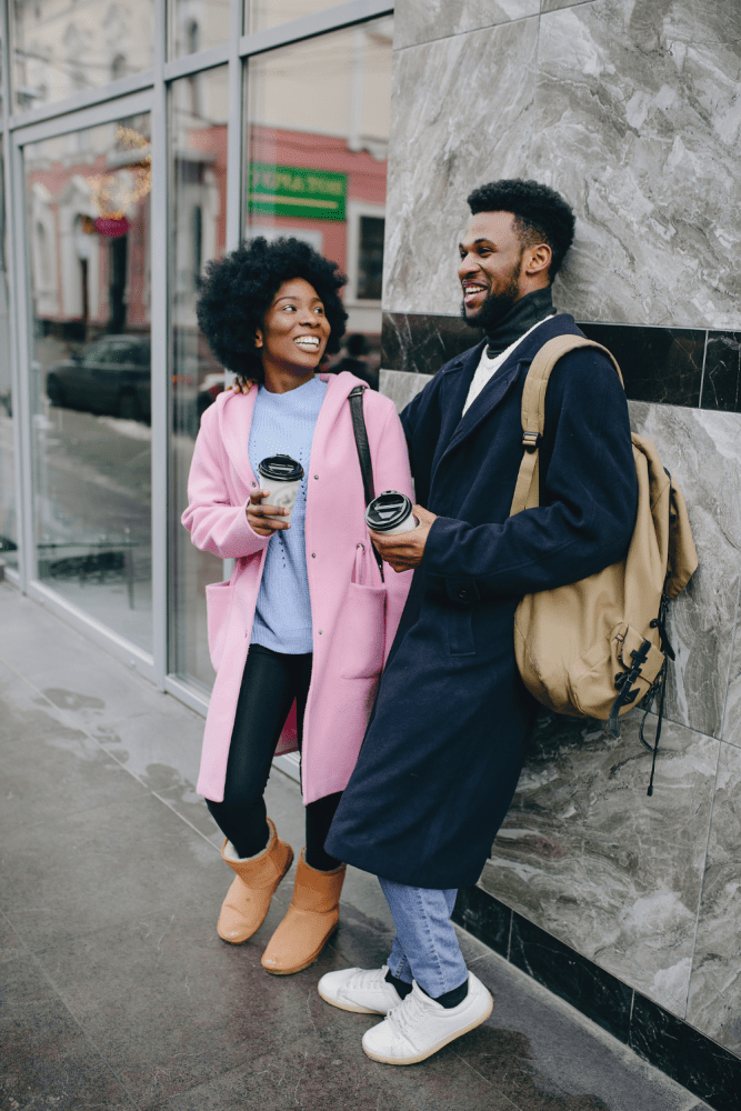 Dating in Your 30s Relationship Advice (Image of a young Black couple standing outside a city building with coffee cups in their hand.)