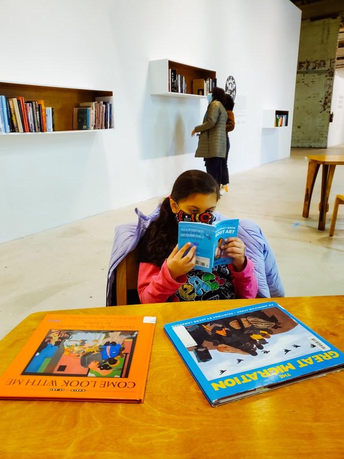 Zhen reading a children's art book at the Black Art Library exhibition in Detroit.