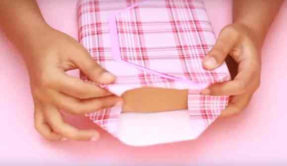 Merapikan sisi bungkus kado bentuk tas