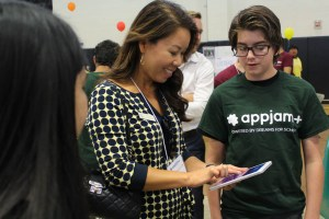 A contest judge checking out a Yorba Linda Middle School team's mobile app.