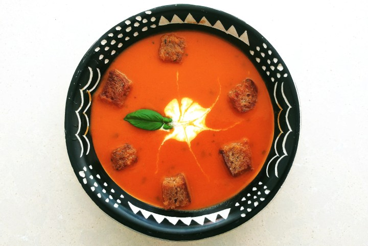 Tomato soup in a black and white ornamental dish, with croutons and, cream and basil decoration.