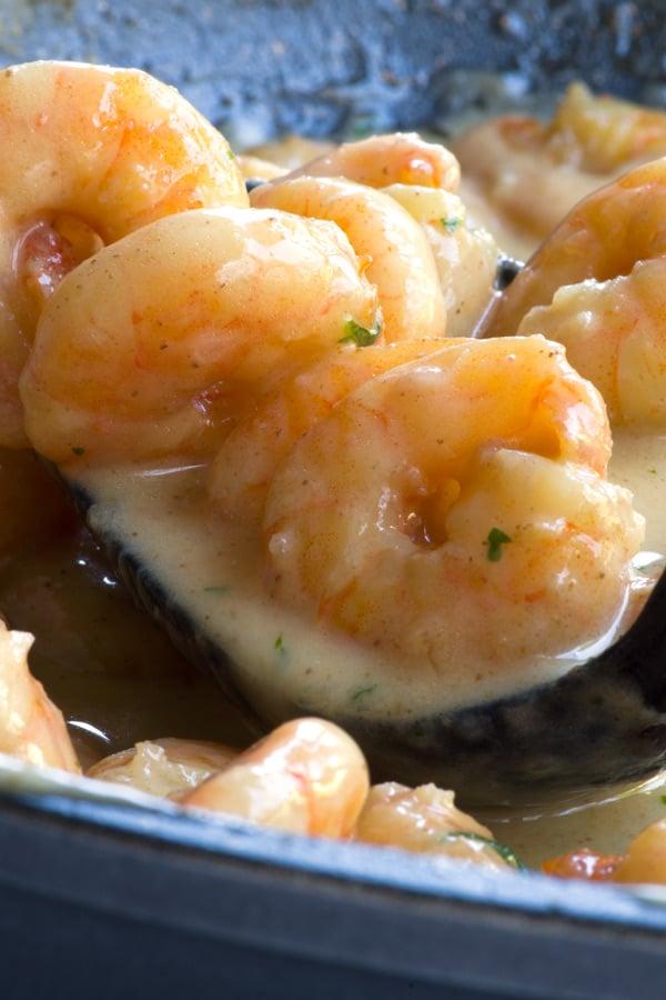 Detail of prawns in cream sauce on a black spoon, in a dark grey pan.