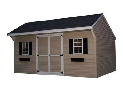 The Vinyl Carriage with a Shingle Roof and two windows with black shutters and flower boxes. Shed has a solid double door