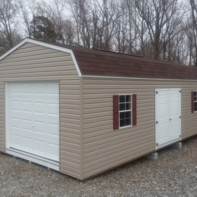 Vinyl shed with brown wood colored shingles and high barn style roof. Has a garage door, a 6 foot fiberglass door, and two windows with maroon shutters