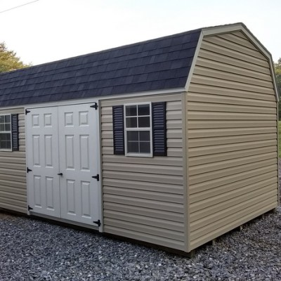 10x16 size vinyl high barn style shed with tan siding, black arch shingle roof, black shutters, 10' ridgevent and 6 foot fiber doors with two windows