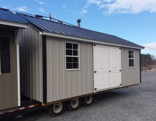 12x20 size metal classic style shed with Gray metal siding, black metal roof, corners and j channel and 6 foot fiber 2 plank doors with two windows