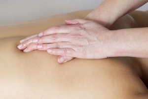 Image of hands massaging a back