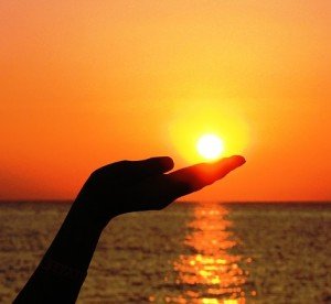 Image of hand holding sun as it sets