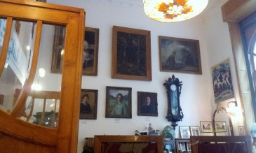 The walls are full of vintage furniture and old paintings