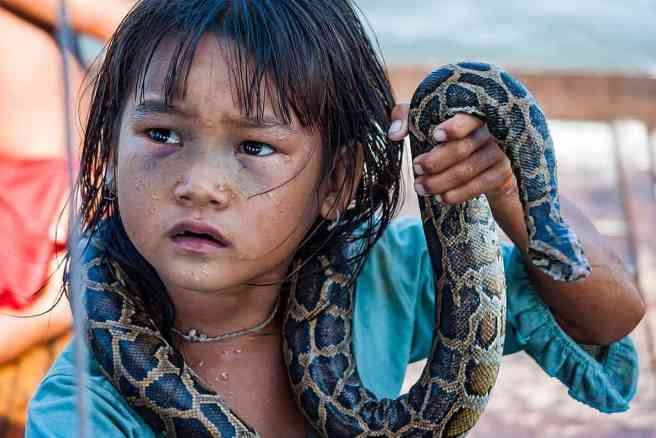 Orphanage tourism and slavery. Tonle Sap, Siem Reap, Cambodia: A little girl making money for her family by posing with a snake in a water village of Tonle Sap Lake. Source: CEphoto, Uwe Aranas https://commons.wikimedia.org/wiki/User:Cccefalon via Wikimedia https://commons.wikimedia.org/wiki/File:Tonle_Sap_Siem_Reap_Cambodia_Girl-begging-for-money-with-snake-01.jpg