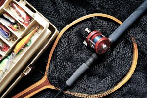 A fishing net, tackle box, and fishing pole.