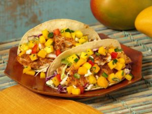 Two tacos stuffed with fish, mangos, and more - looking delicious on a plate.
