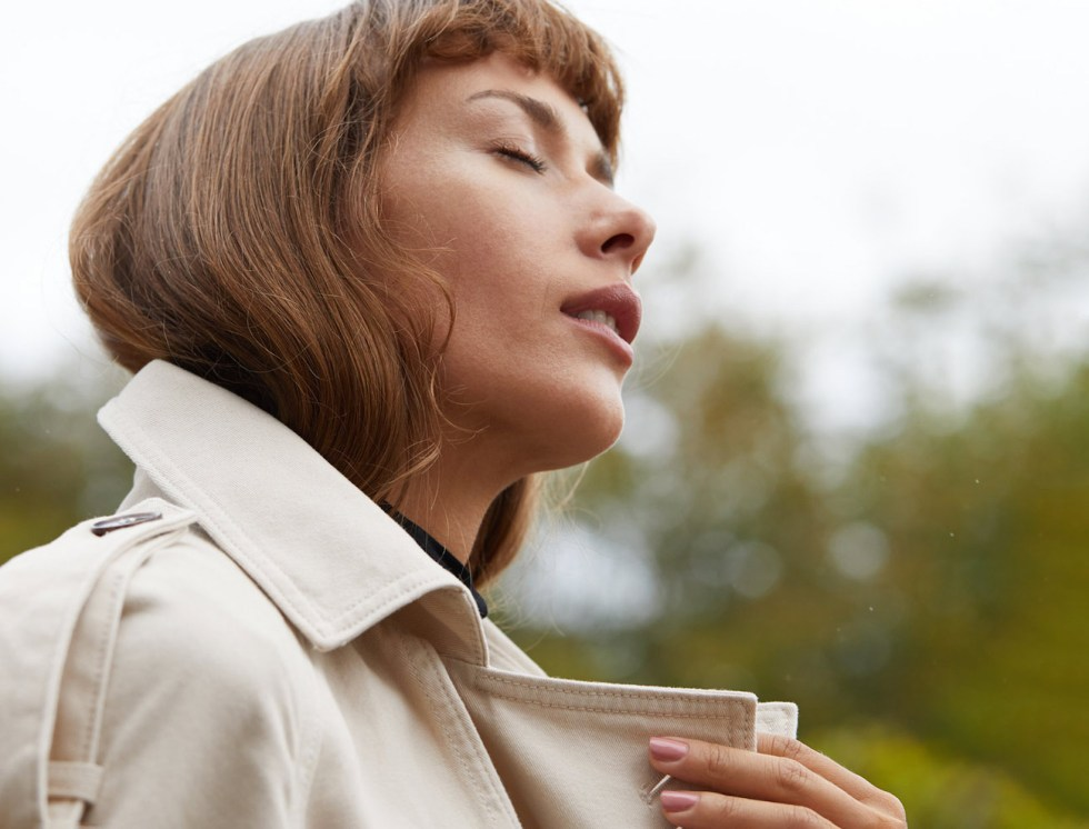 woman closing her eyes outside