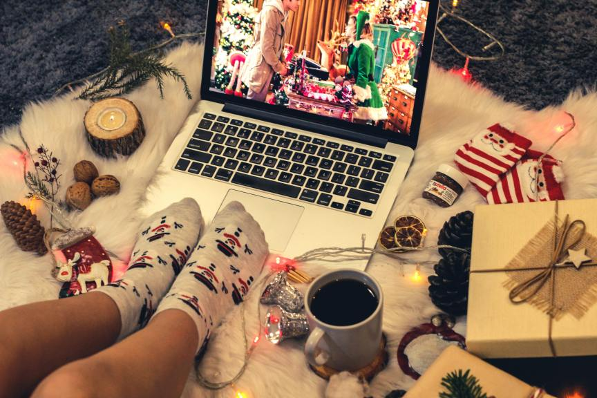 Feet wearing Christmas socks cozied up to laptop playing a holiday show surrounded by festive decorations and a mug of coffee