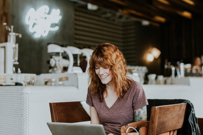 happy woman with red hair working on laptop in coffee shop