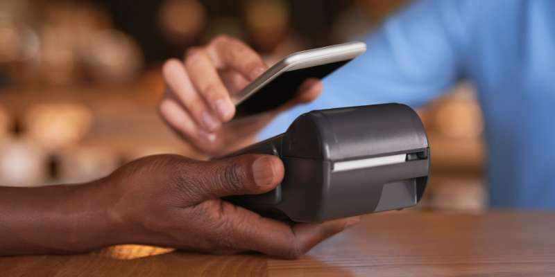 hand of a person using their phone to complete a tap-to-pay transaction while another hand holds the card terminal