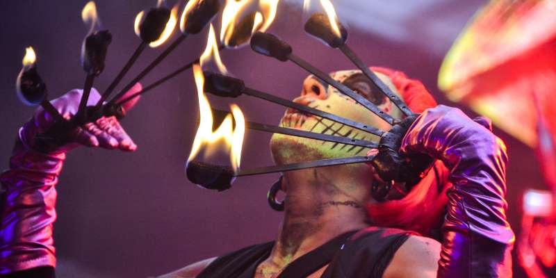 circus performer with skull makeup blowing on multiple fire batons held in front of their face