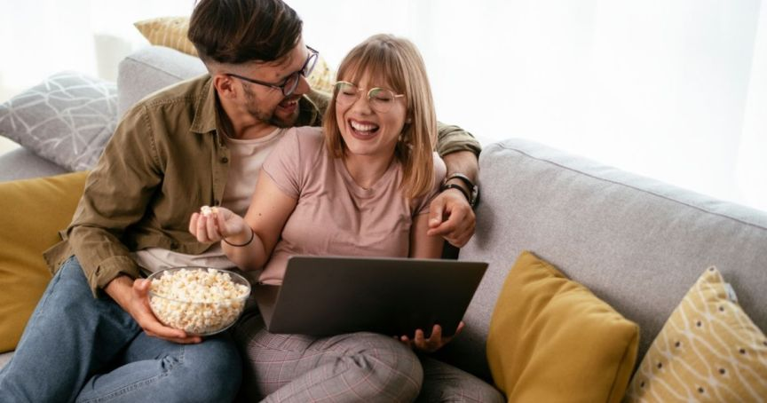 Happy couple watching event content on their laptop