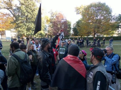 Counter-protesters tear up a Nazi flag.