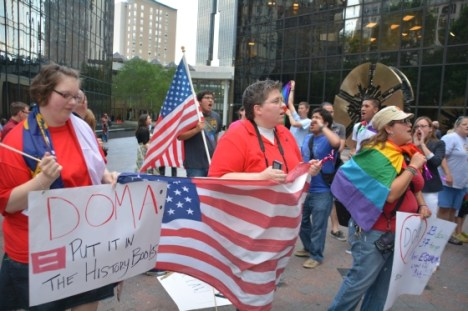 At left, Ashley Gainey and Brandi Morris stand with protest signs and a U.S. flag amid an Uptown Charlotte rally on Wednesday celebrating Supreme Court decisions on same-sex marriage . Photo Credit: rcraigsnider@gmail.com