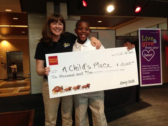 A Child's Place Student Adovocate Kelly Cates and child actor Kenneth smile for the cameras  after winning over Wells Fargo employees' votes for a $10,000 grant at a  Sept. 13 'Flash Philanthropy' mixer in Uptown Charlotte.